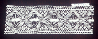 Fragment with a row of diamond shapes containing oblong ovals. Irregular mesh ground surrounds motifs.