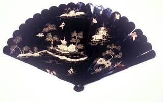 Brisé fan of black lacquered wood with gilt decoration. On the obverse, an island with houses and a pagoda. On the reverse, islands with houses and a small bridge.