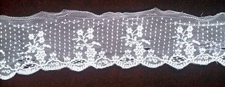 Net band with tambour embroidery in floral spray design. Border of small ovals forms scallop along bottom edge. Tiny dots over ground.