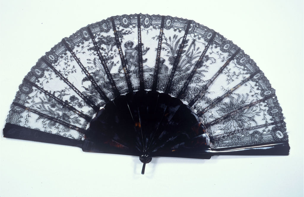 Pleated fan with unbacked black lace leaf showing putti in a landscape. Plain tortoise-shell sticks and guards.