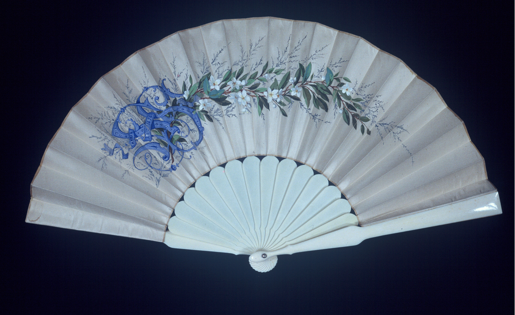 """Pleated fan, leaf of white silk with the obverse decorated with a spray of orange blossoms and a monogram: """"SS April 26, 1876"""" painted in gouache. Reverse is blank. Sticks are plain white celluloid."""