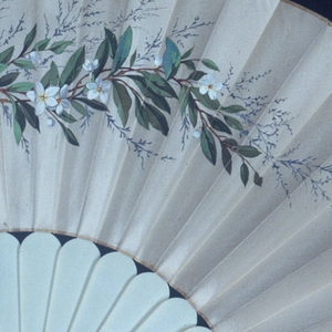 "Pleated fan, leaf of white silk with the obverse decorated with a spray of orange blossoms and a monogram: ""SS April 26, 1876"" painted in gouache. Reverse is blank. Sticks are plain white celluloid."