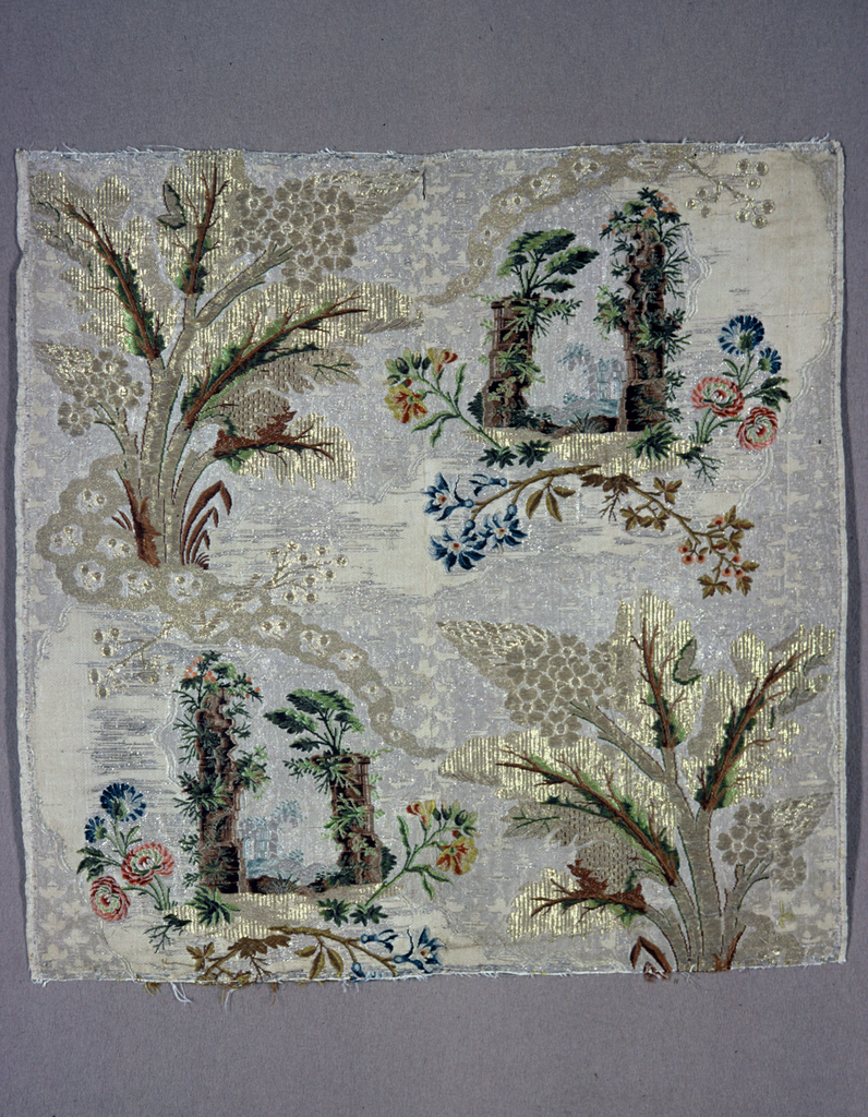 Panel of cream and silver fabric heavily brocaded with gold thread and multicolored silks. Pattern has architectural ruins and flowers in the lower left and upper right corners while the lower right and upper left corners have trees with decorative foliage.