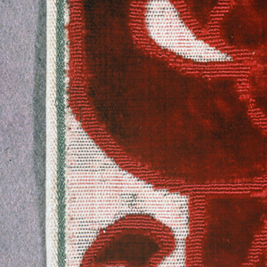 Fragment of red cut and uncut velvet on a silver metallic ground. Fragment shows portion of a large-scale floral motif.