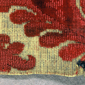 Fragment of red cut and uncut velvet on yellow silk ground with extra metallic weft. Two portions of curving large-scale foliage are all that show of the design.
