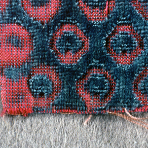 Fragment of blue cut and uncut velvet on rose silk ground. Design in velvet forms hexagonal-shaped areas each enclosing a tiny blossom.