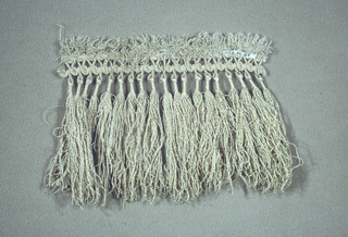 Cream-colored silk fringe - short fringe on upper edge over border corded in scroll design - threads crinkly - groups of threads wrapped together for short distance below upper border.