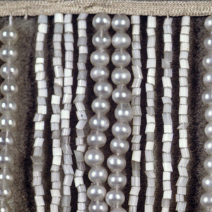 Alternating strings of imitation pearl beads and white glass beads suspended from a narrow white silk band.