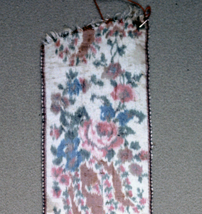 Ivory ground with groups of flowers warp-printed in rose, blue, brown and green. Brown picot edges.