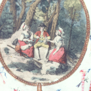 """Handscreen with a paper leaf and turned wood handle. Obverse: oval medallion with a hand-colored engraving showing two couples eating a meal in a landscape, surrounded by a border of hand-painted musical instruments. Reverse: printed with dialogue from the comic opera """"Les Solitaires de Normandie."""""""
