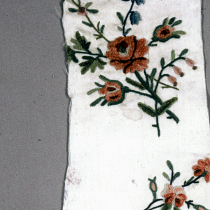 Shaped fragment of white satin embroidered in colored silks and chenille; design, floral sprays enclosed by flowering stems.
