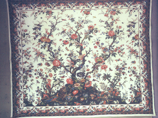 Mezzaro in a multicolored design on a white ground. Central large-scale tree with many different blossoms. Small flanking tree on either side. Floral sprays, insects, birds, and animals scattered over the ground. Border of massed flowers and fruit with perching brids. Urns and vases in foreground.
