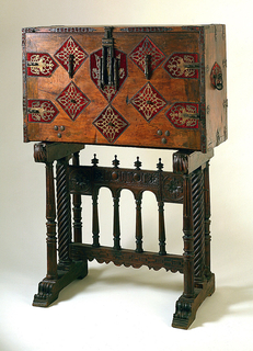 Rectangular chest, the drop front with diamond and losenge-shaped decoration covered in worn red velvet; pierced wrought iron hinges, mounts, lock and handles; drop front opens to reveal multiple drawers with columnar and other architectonic decoration. Interior relined. (Shown with trestle stand 1968-140-7).