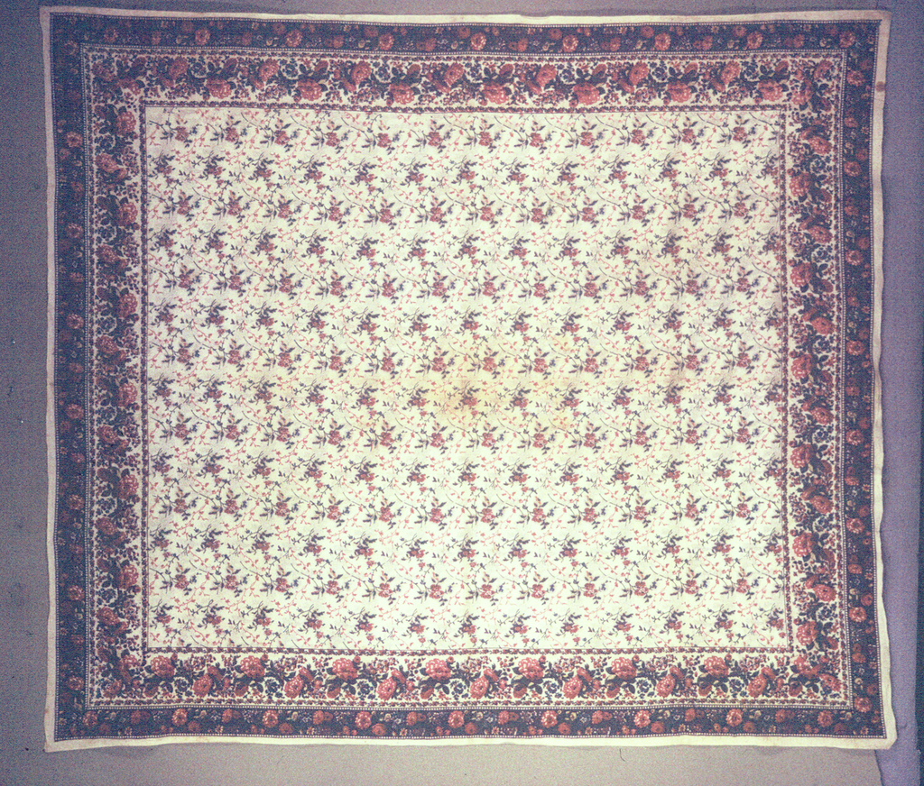 Mezzaro in a multicolored design on a white ground. Floral sprays and slender vines in an allover pattern. Secondary floral design in small black dots. Double floral border.