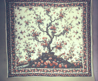 Mezzaro in a multicolored design on a white ground. Central large-scale tree with many different blossoms. Small flanking tree on either side. Floral sprays, insects, birds and animals scattered over the ground. Double floral border.