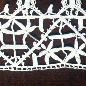 Strip of reticella insertion and border, made separately and stitched together. Insertion design has zigzag lines setting off triangular areas which have rosettes.