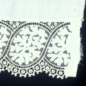 Applique and embroidery on net. Part of a border with a floral pattern white-on-white.
