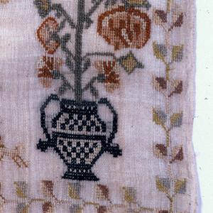 Ornamental border enclosing alphabet, vases of flowers, birds, and Adam and Eve.