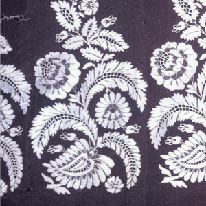 Lace showing a pattern of sprays of flowers and leaves forming a band above a narrow border of conventionalized flowers.