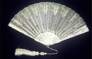 Pleated fan. Leaf of white gauze with applied white taffeta, gilt and green spangles. Sticks are mother-of-pearl with gilt and green piqué. White cord and tassel.