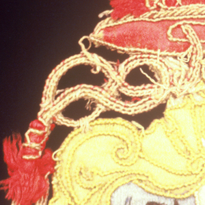 Design of cardinal's hat with seven tassels on each side surmounting a coat of arms composed of a blue shield with a black bird in each quarter on which is a small red shield with a griffin(?) and part of a sunburst; yellow mantling.