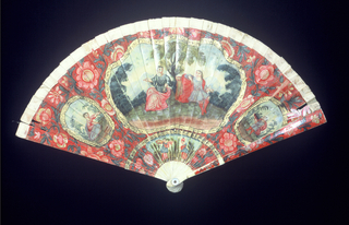 Brisé fan. Painted and gilded ivory sticks showing a central cartouche enclosing a seated man and woman against a landscape. Two flanking ovals, one enclosing a girl, the other a boy. These are set against a red ground decorated with flowers. Below is a scene with two flowers. Reverse: similar arrangement with crudely painted trees.