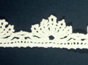 Narrow lace with scallop on one edged formed of five loops radiating from central point.