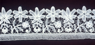 Duchesse style lace in pattern of open flowers with leaves.