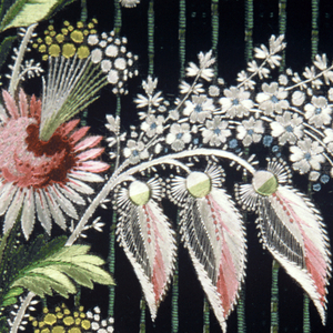Black velvet with green stripe and floral sprays in white, rose and green. Lace at edge.