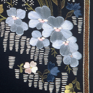 Black taffeta embroidered with a border or lapel design in a pattern of small naturalistic flowers sprays in white, blue, pink and green.