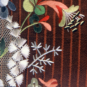 Multicolored embroidery in a floral design with net appliqué on a brown ground fabric.