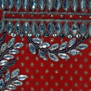 Formal floral pattern embroidered with silver and gold wire, green and gold sequins and glass beads on a bright red velvet ground with dots of gold in the ground.