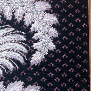 Dark purple ground with a small diagonal design embroidered in a border pattern of heavy foliage sprays in silver sequins and metal wire.