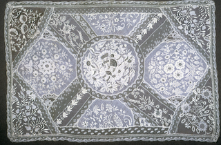 Rectangular table scarf with round center piece and two five-sided pieces embroidered finely in white cotton floral design. Corners and filler pieces in embroidered net; lace edging.