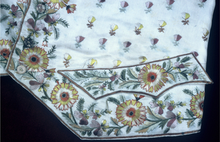 Man's short waistcoat with standing collar, notched hem and pocket flaps. In white silk satin embroidered with an all-over design of small floral sprigs and densely embroidered on the front and lower edges with floral vine, in pale blues, greens and yellows.