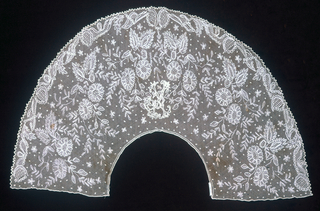 """Deep round collar of net with an alloever embroidered floral design. Sawtooth scallops and tiny dots powdered over the ground. Initial """"C"""" embroidered in center back."""
