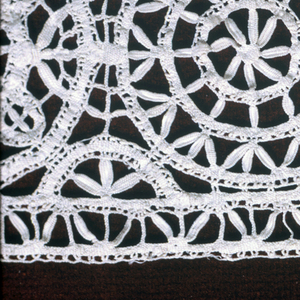 Strip of insertion lace in design of concentric circles, each with central rosette.