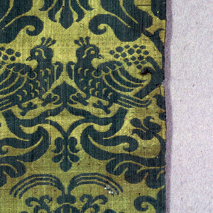 Reversible design in green and gold-colored silk of symmetrical pattern in alternating horizontal rows. One row has three tulips crowning a pedestal formed by curving bands that have pairs of confronted birds. The other row has a fountain of a highly stylized animal forms.