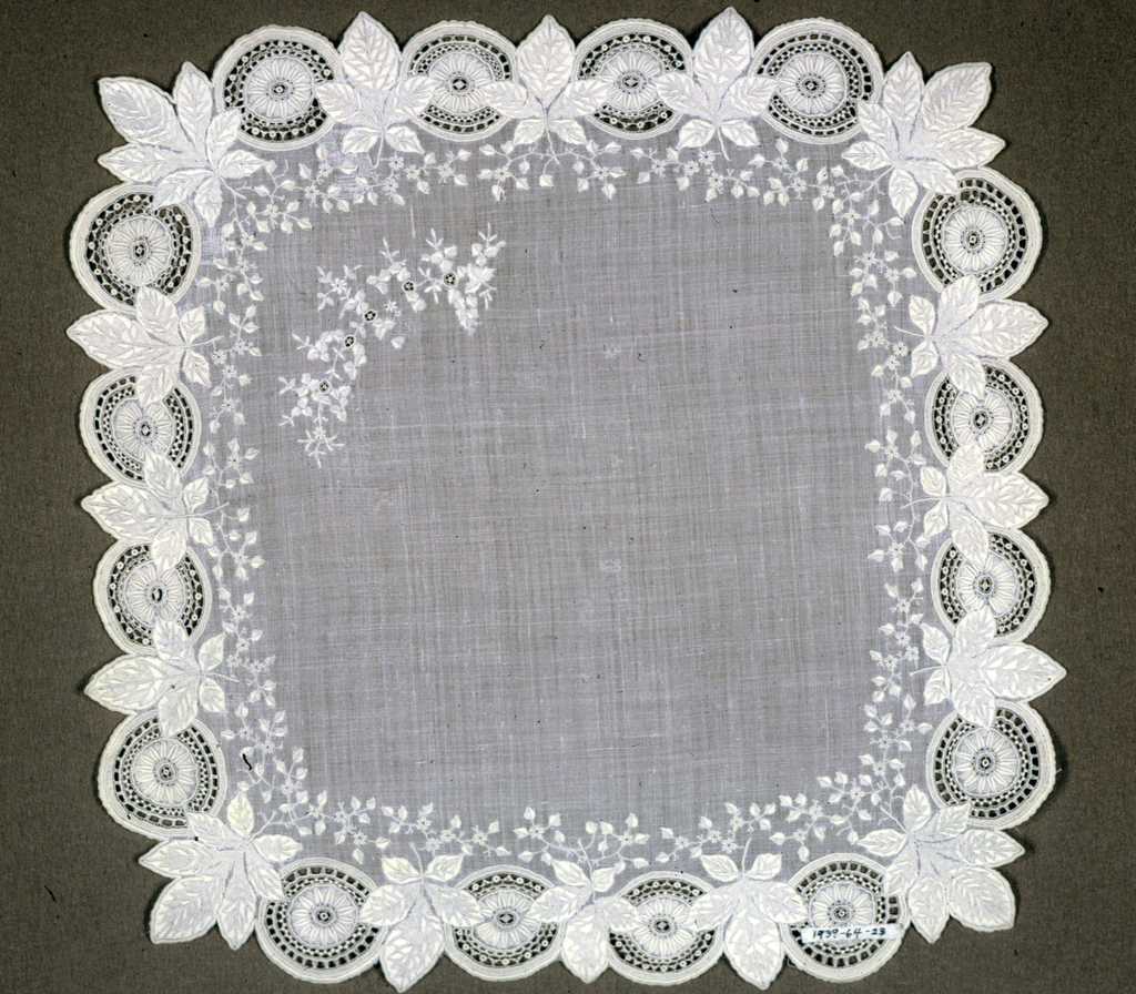 Linen handkerchief with embroidered floral band and border of leaves and wheels alternating.