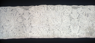 Design showing medallions of Madonna and Child set into floral pattern. The upper edge originally scalloped has been filled in to form a straight edge.
