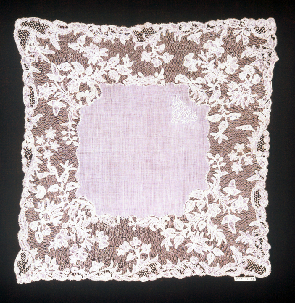 Linen center with the embroidered initials J.M.N. and border of bobbin lace in design of flowering branches.