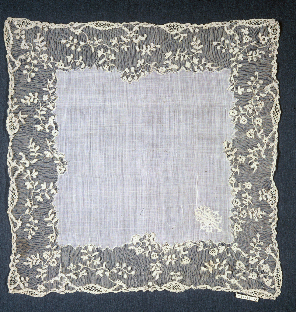 Linen center with monogram J.M.N. and border of Mechlin lace in design of pendant flowers.