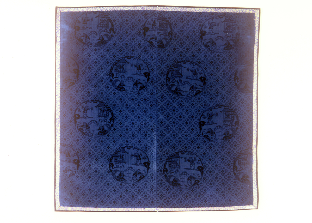 Square panel of deep blue velvet. Uncut ground with the design in cut pile of small-scale cloud motifs arranged to form quatrefoil and large medallions, each enclosing a scene showing four men engaged in the same activities: fishing, gathering firewood and reading. Edges bound with gold and blue compound satin. Backed with light blue cotton plain weave cloth.