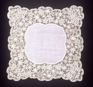 Linen center with deep border of bobbin lace resembling Brussels/ Honiton style; in design of flowers and leaves.