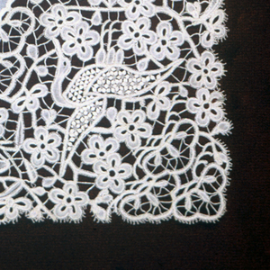 Linen center with deep border of bobbin lace resembling Brussels/Honiton style; in design of flowers, birds and ornamental forms similar to bow-knots.