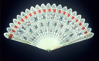 Brisé fan. Ivory sticks carved and pierced in conventional design and painted in floral ornament. Red satin ribbon.