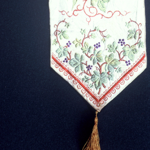 """White ribbon with a spray of roses, lilies and curling vines of ivy entwined within the words """"Happy May Thy Future Be."""" Finished at the bottom with yellow tassel."""