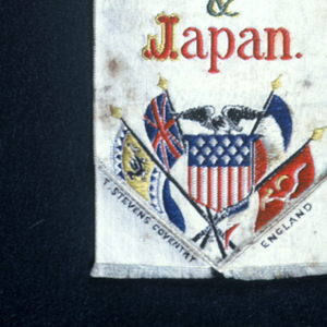 """White ribbon with a griffin on a plinth with the word """"Trademark"""" inscribed on it. Below: """"Robert K. Davies & Co. New York Novelties from England, France, China & Japan."""" American shield flag with an eagle is surrounded by the flags of each of the four nations."""