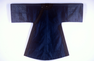 Woman's gown with long sleeves, closing diagonally across the shoulder and under the right arm. Made of dark blue silk gauze with medallions of leaf and fret patterns. Trimmed with black silk bands. Fastenings are four silk frogs with spherical brass buttons.