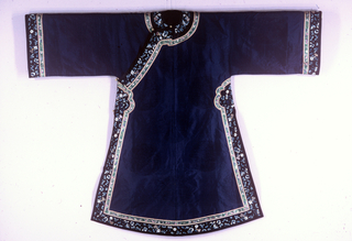 Robe closing diagonally across the shoulder and under the right arm. Made of dark purple silk in gauze weave with medallions of dragons and floral designs. Trimmed with a wide black silk band embroidered in shades of blue with flowers, butterflies, and auspicious symbols; and a narrow green band woven with floral designs. Fastenings are four silk frogs with four spherical brass buttons.
